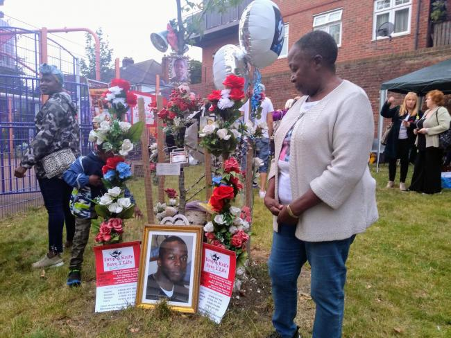 Sophie Kafeero standing by her son Derick\'s memorial on the Cambridge Estate in Kingston. Credit - LDR Sian Bayley.
