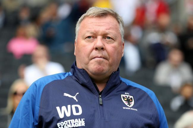 Wimbledon manager Wally Downes has been suspended after being charged with betting offences