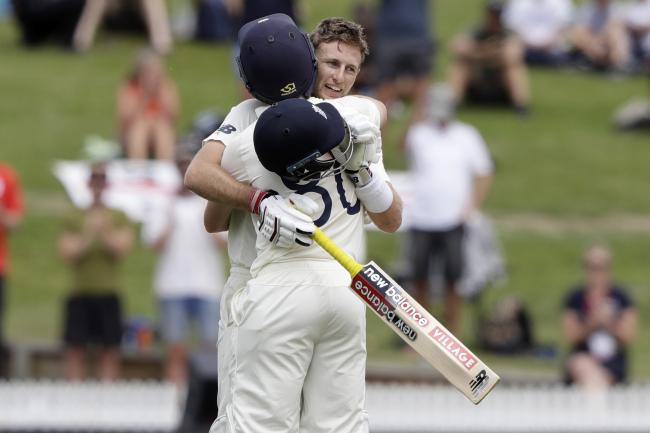 England's Joe Root, right, is congratulated by teammate Ollie Pope