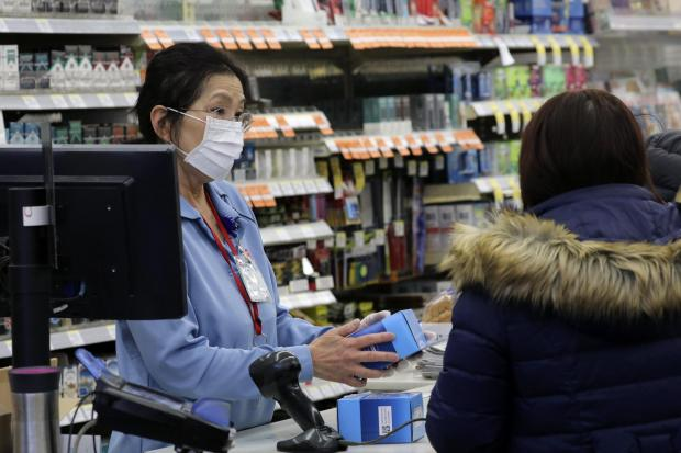 Your Local Guardian: A sales clerk at a pharmacy rings up a purchase of face masks as fears of the coronavirus continue