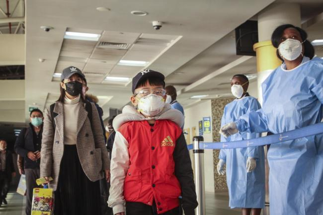 Passengers arriving from a flight from Changsha in China are screened for the new type of coronavirus