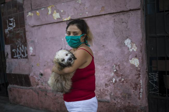 A woman wearing a face mask cradles her dog as she walks in Lima, Peru