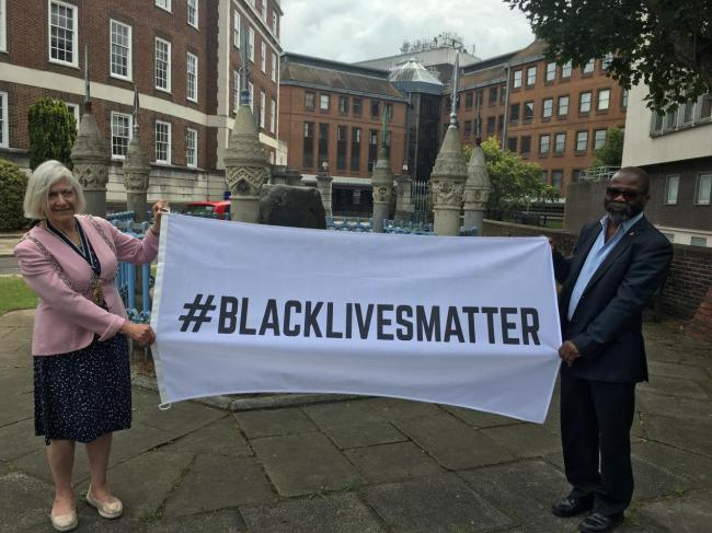 Mayor of Kingston Councillor Margaret Thompson and CEO of Kingston Race Equality Council John Azah with the Black Lives Matter flag at the Guildhall, Kingston. Credit: Kingston Council