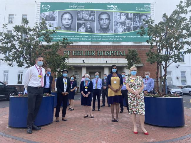 Epsom Hospital staff gather in front of the giant banner voicing the hospital's commitment to anti-racism.