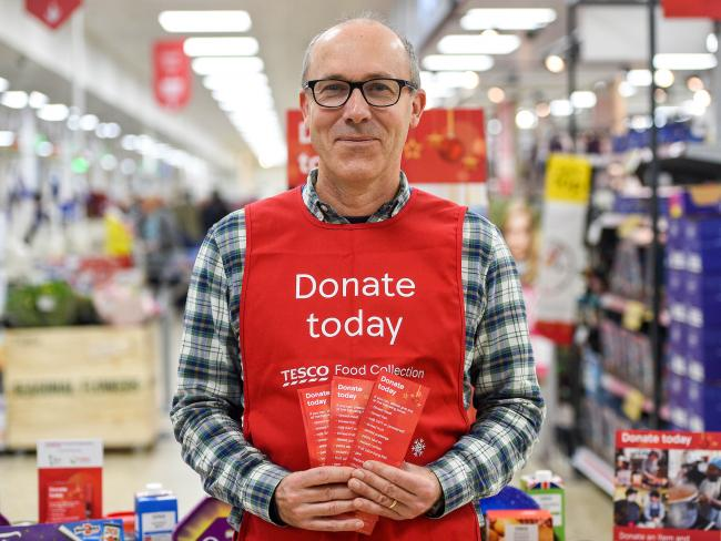 A Tesco volunteer holding a guide for donations at the launch of the Tesco Food Collection in the Surrey Quays Extra store.