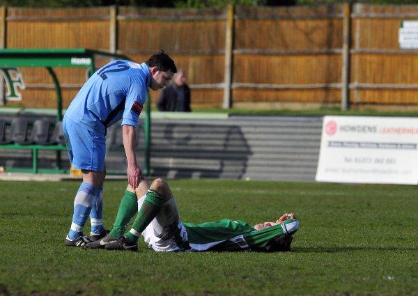 Down and out: Kingstonian's Bobby Traynor consoles Leatherhead's Harry Ottaway after relegation