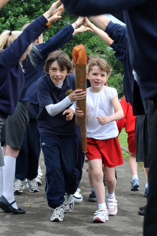 Excited children hold an Olympic torch relay and community event
