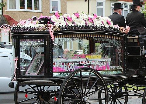 A horse drawn carriage bedecked in pink and black carries Tia's body to her funeral
