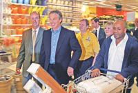 Trolley dollies: Prime Minister Tony Blair takes an unsuspecting shopper by surprise