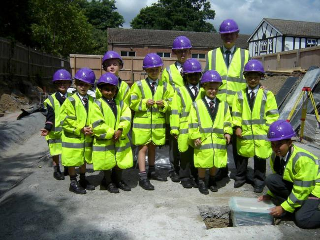 Schoolboys bury time capsule in foundations of new school building