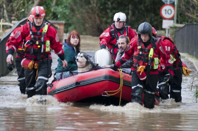 A couple and their pets are rescued by boats from their home in Thorncroft Drive on Christmas Eve