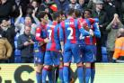 Happy days: Crystal Palace striker Wilfried Zaha is mobbed after grabbing the decisive goal in Saturday's 1-0 win over Stoke City