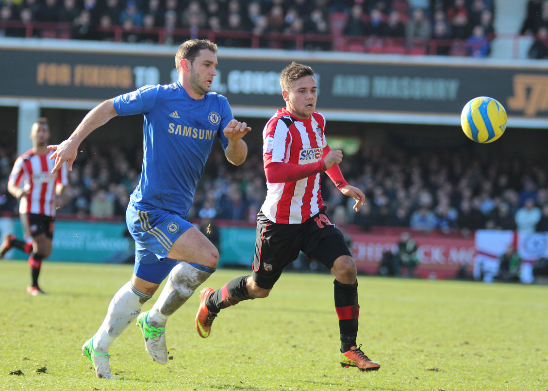Branislav Ivanovic chases Brentford's Harry Forrester in the FA Cup 4th Round at Griffin Park in 2013