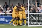 Happy days: Bedsente Gomis is mobbed after making it 2-0 against Macclesfield Town on Saturday