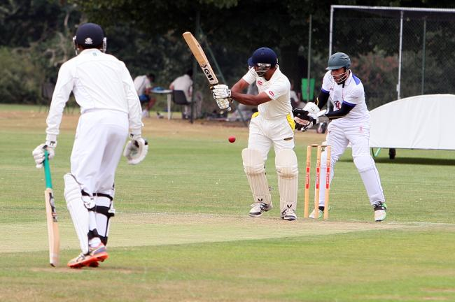 Making hay: Cobham's AK Tyrone cuts loose as Kingstonian skipper and wicketkeeper Amir Hussain looks on
