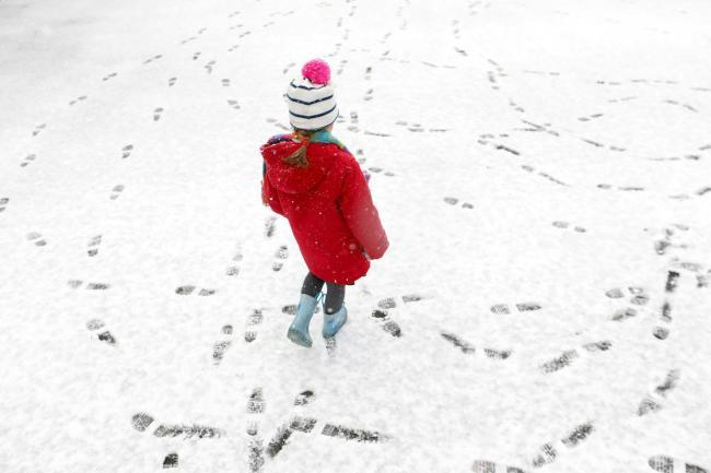 Five year old Scarlett Cox plays in the snow on her way to school in Tunbridge Wells, Kent (Philip Toscano/PA)