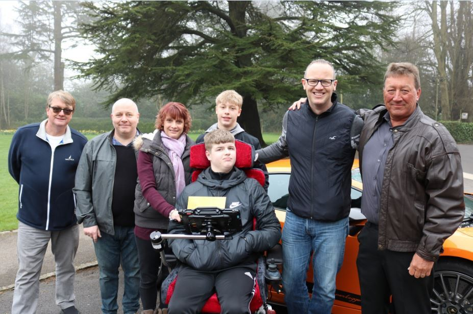 The Briston family with the supercar drivers and their golden ticket to The Supercar Event at The Children's Trust, Surrey.