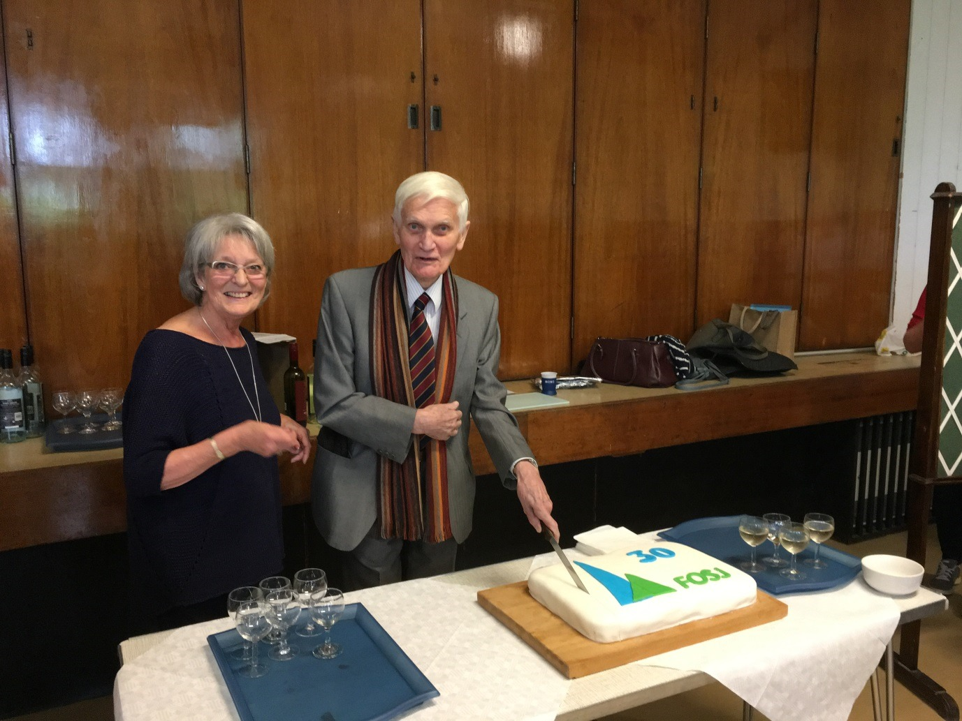 Reverend John Green cuts the birthday cake beside chairwoman of Friends of St. James' Church, Margaret Wicks