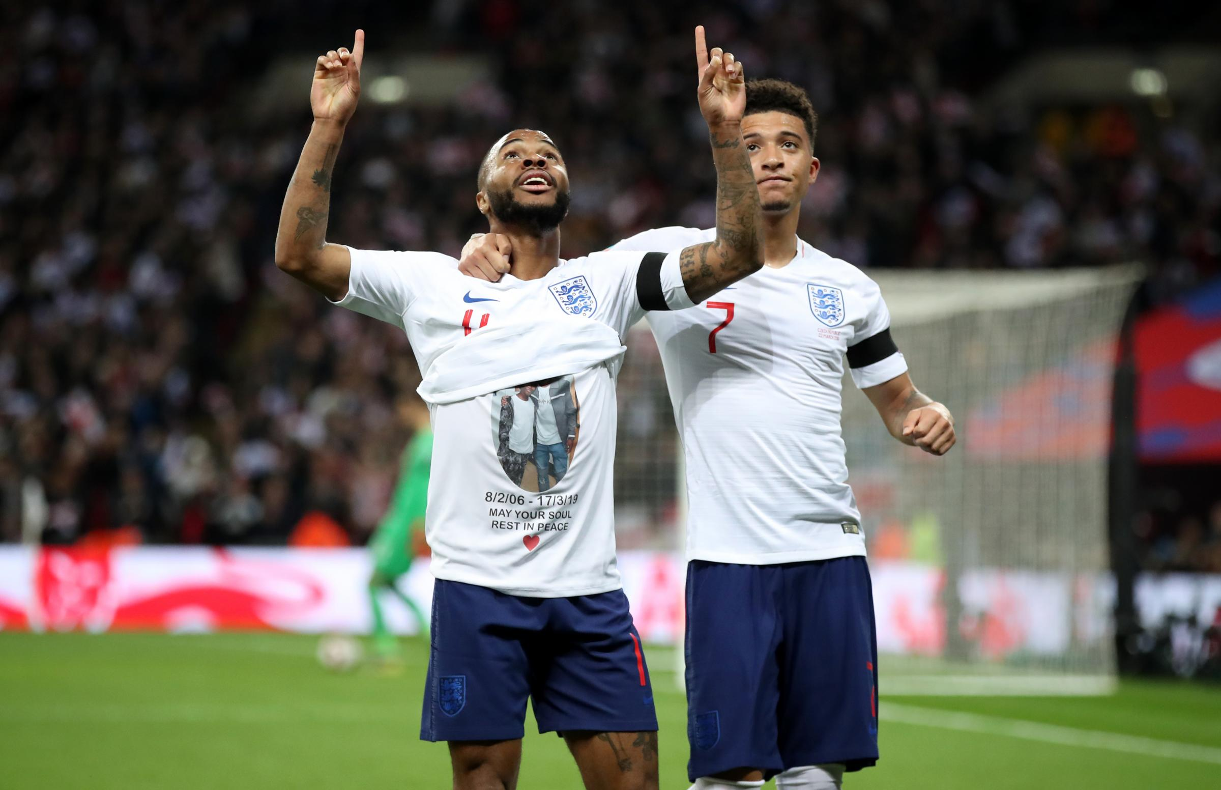England's Raheem Sterling celebrates scoring his side's third goal of the game and shows a t-shirt in memory of former Crystal Palace youth player Damary Dawkins during the UEFA Euro 2020 Qualifying,   (Photo credit : Nick Potts/PA Wire. )