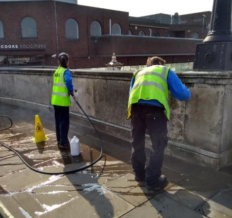 Neighborhood Rangers removing offensive graffiti on a bridge in the town centre. Image: RBK via Twitter